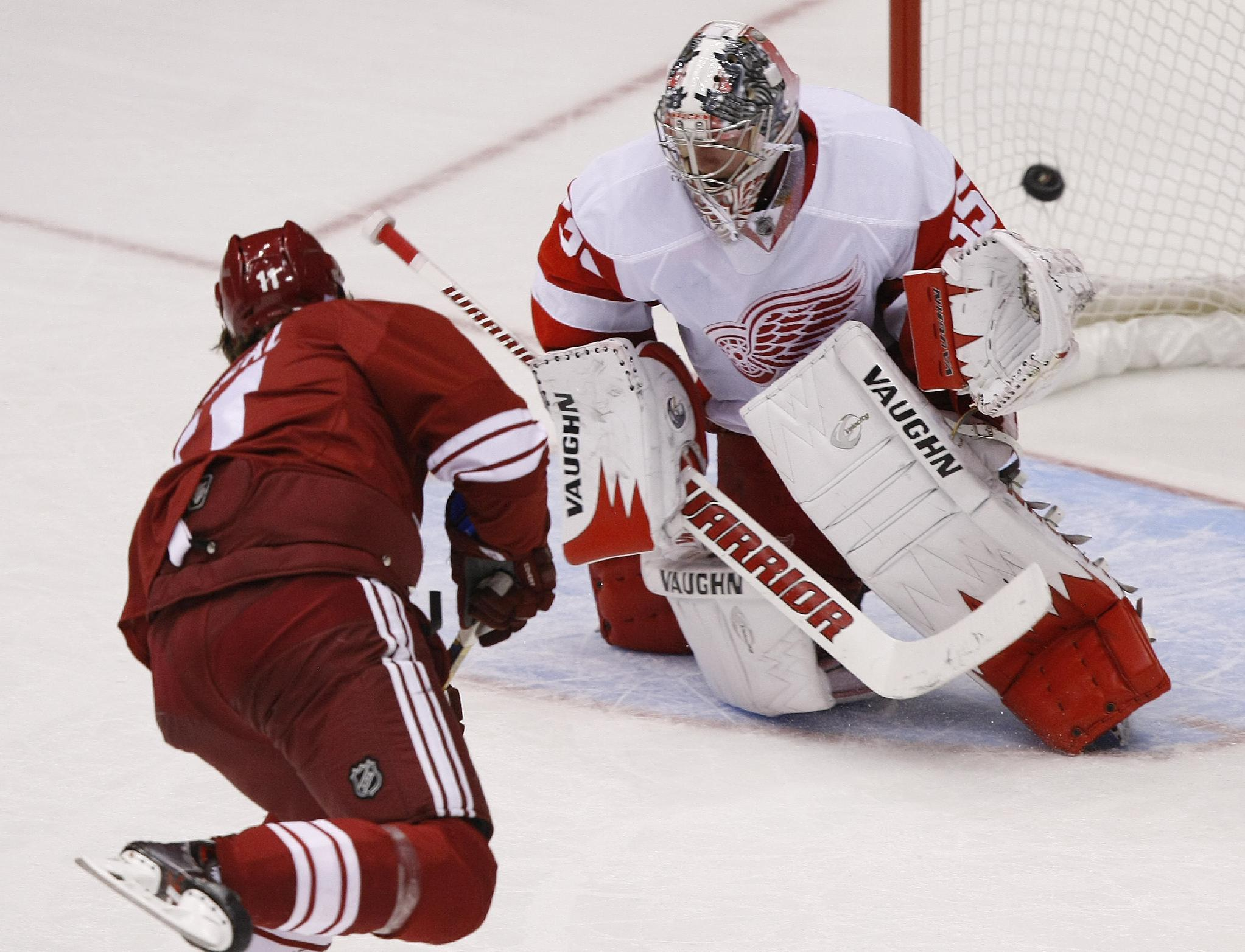 Phoenix Coyotes center Martin Hanzal (11), left, scores a third period goal on Detroit Red Wings goalie Jimmy Howard (35) during an NHL hockey game on Saturday, Oct. 19, 2013, in Glendale, Ariz