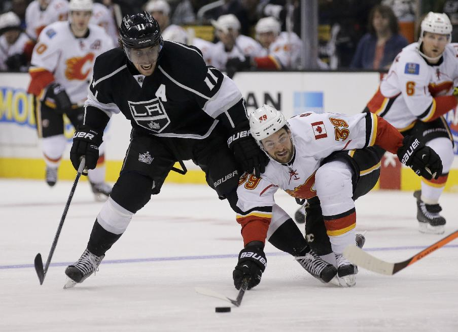 Los Angeles Kings center Anze Kopitar, left, battles Calgary Flames left wing T.J. Galiardi for the puck during the second period of an NHL hockey game in  Los Angeles, Monday, Oct. 21, 2013