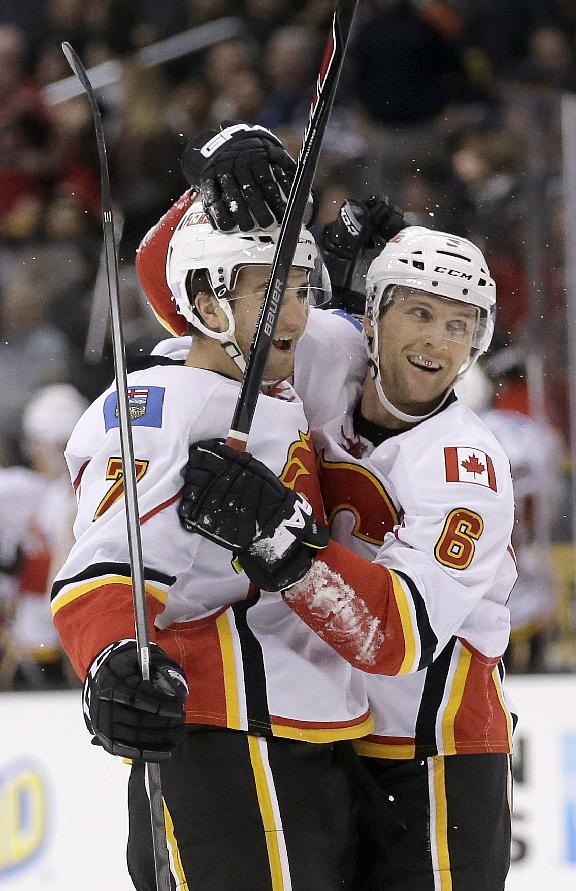 Calgary Flames defenseman T.J. Brodie, left, celebrates his game winning goal with defenseman Dennis Wideman against the Los Angeles Kings during the third period of an NHL hockey game in  Los Angeles, Monday, Oct. 21, 2013. The Flames won 4-3