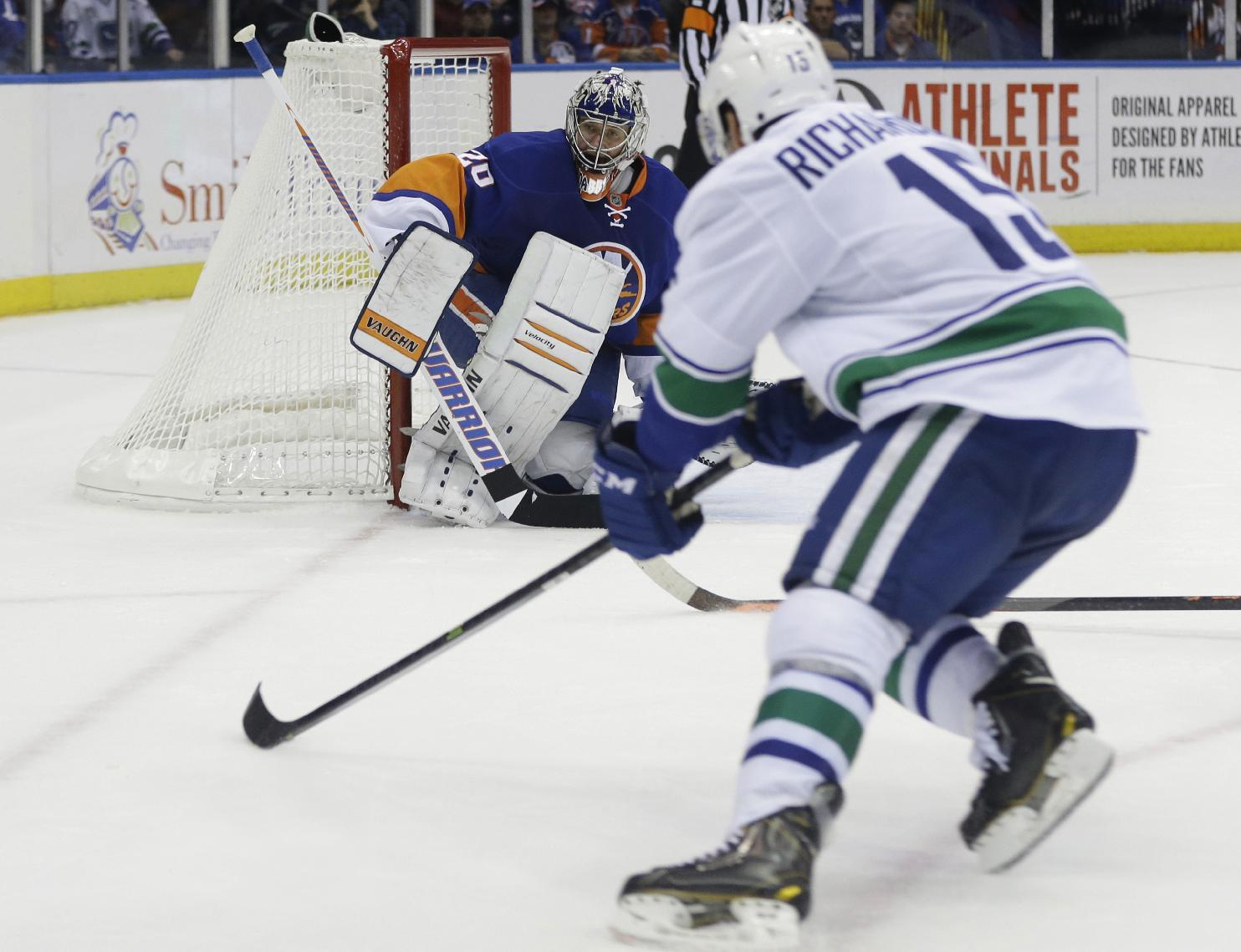 New York Islanders goalie Evgeni Nabokov (20) watches as Vancouver Canucks' Brad Richardson (15) shoots the puck to win the game during the overtime period of an NHL hockey game Tuesday, Oct. 22, 2013 in Uniondale, N.Y. The Canucks won the game 5-4