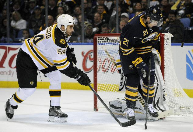 Boston Bruins defenseman Adam McQuaid (54) chases Buffalo Sabres right winger Drew Stafford (21) as he eyes an incoming shot during the first period of an NHL hockey game in Buffalo, N.Y., Wednesday, Oct. 23, 2013