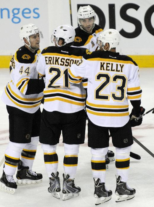 Boston Bruins' Loui Eriksson (21), of Sweden, is helped off the ice by Bruins' Dennis Seidenberg (44), and Chris Kelly (23) after a hit to the head by Buffalo Sabres' John Scott during the third period of an NHL hockey game in Buffalo, N.Y., Wednesday, Oct. 23, 2013.Boston won 5-2
