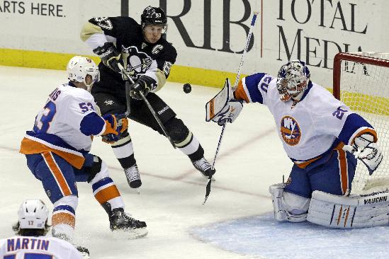 New York Islanders goalie Evgeni Nabokov (20) blocks a shot as Pittsburgh Penguins' Sidney Crosby, center, tries to bat the rebound in front of Casey Cizikas (53) during an NHL hockey game in Pittsburgh, Friday, Oct. 25, 2013