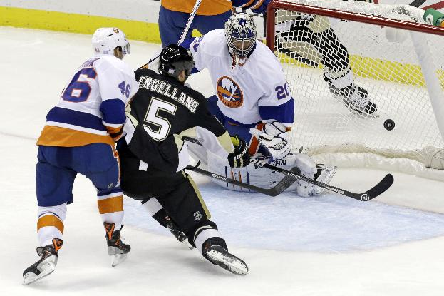 Pittsburgh Penguins'  Deryk Engelland (5) beats New York Islanders' Matt Donovan, left, and puts a shot behind Islanders goalie Evgeni Nabokov for a goal in the third period of an NHL hockey game in Pittsburgh, Friday, Oct. 25, 2013. The Islanders won 4-3