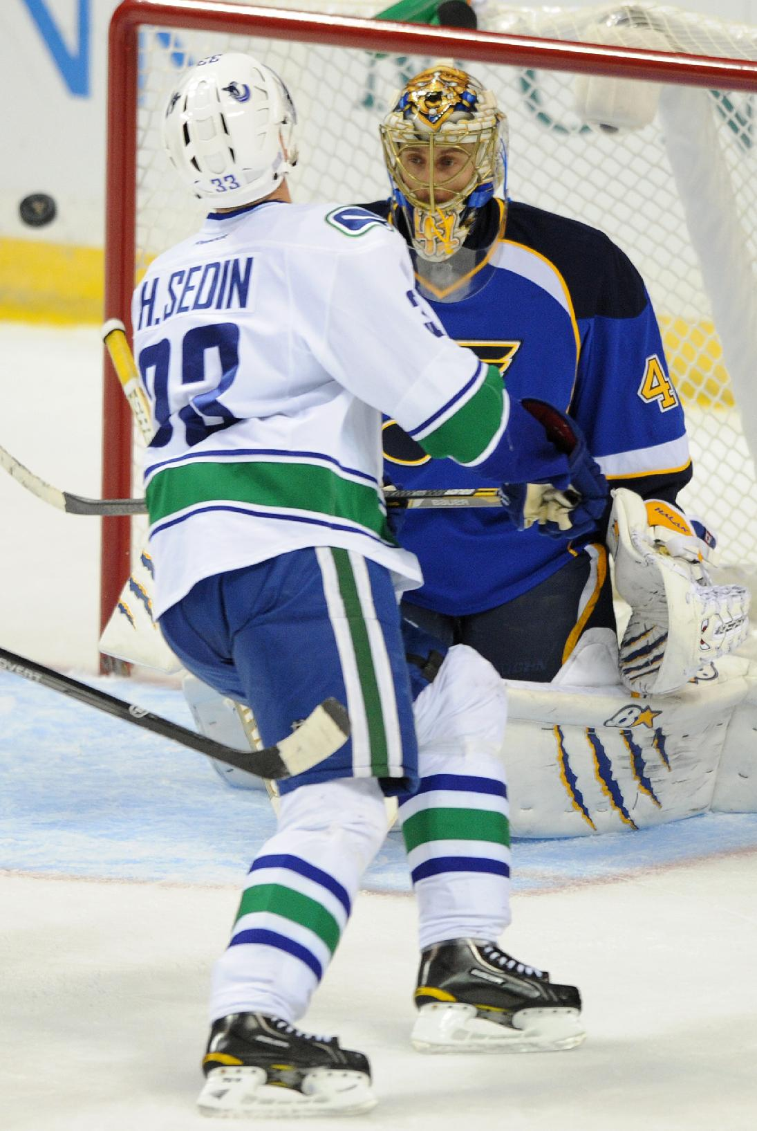 St. Louis Blues' goalie Jaroslav Halak (41), of Slovakia, blocks a shot by Vancouver Canucks' Henrik Sedin (33), of Sweden, during the third period of an NHL hockey game on Friday, Oct. 25, 2013, in St. Louis