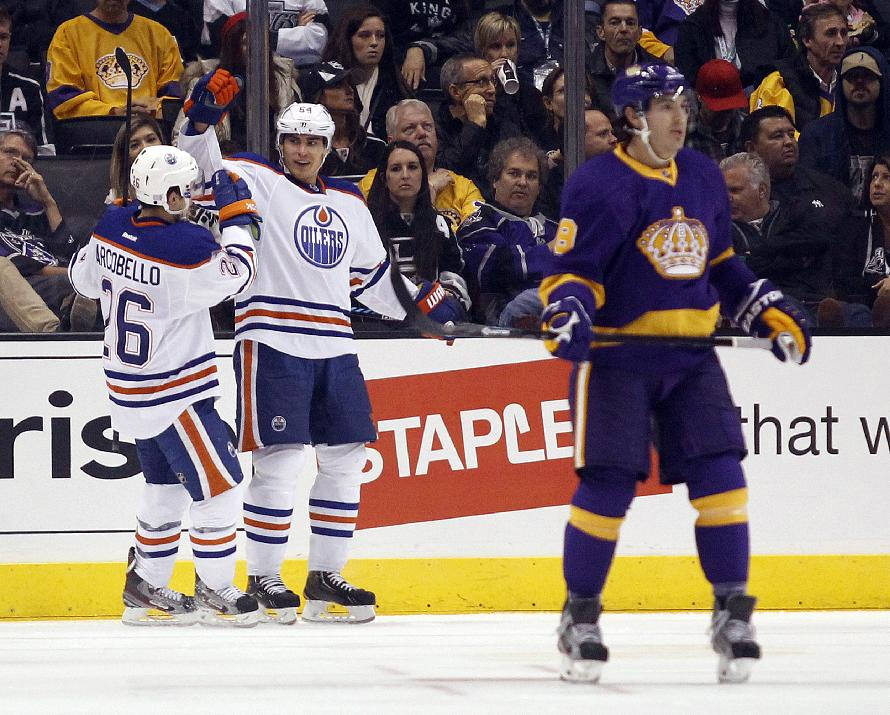 Edmonton Oilers left wing Mark Arcobello (26) celebrates a goal by Oilers right wing Nail Yakupov, center, of Russia as Los Angeles Kings defenseman Drew Doughty, right, skates back to the bench during the second period of an NHL hockey game Sunday, Oct. 27, 2013, in Los Angeles