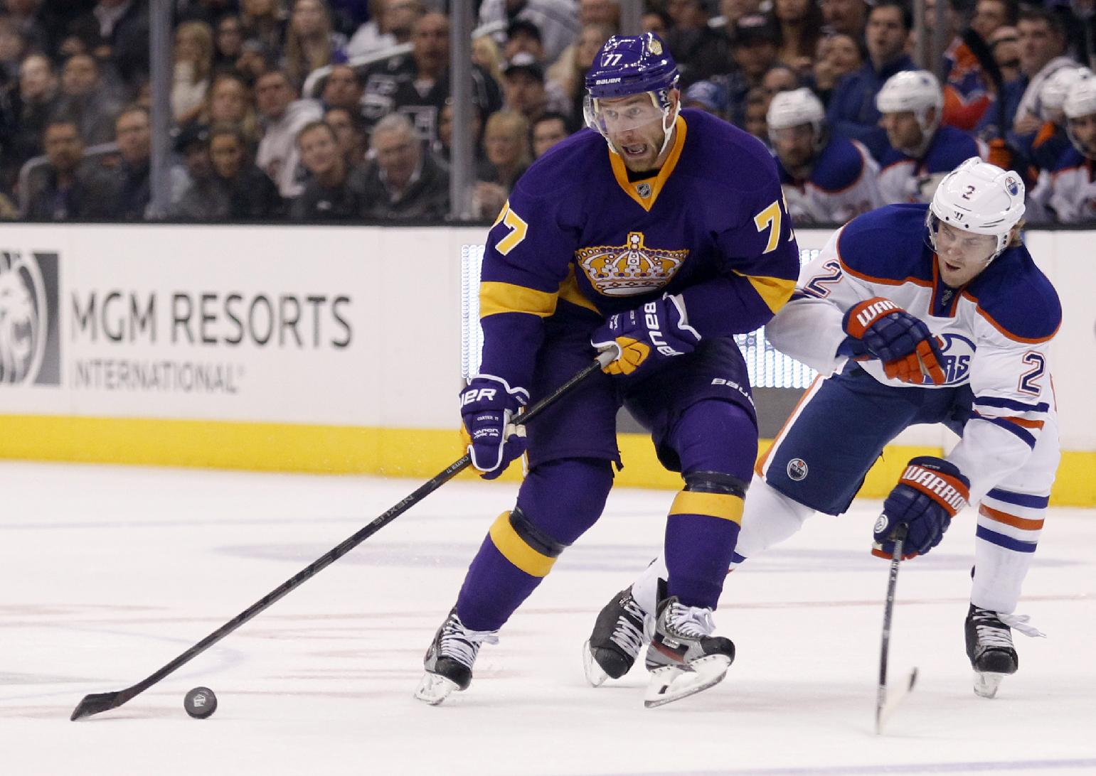 Los Angeles Kings center Jeff Carter (77) battles Edmonton Oilers defenseman Jeff Petry (2) for control of the puck during the second period of an NHL hockey game Sunday, Oct. 27, 2013, in Los Angeles