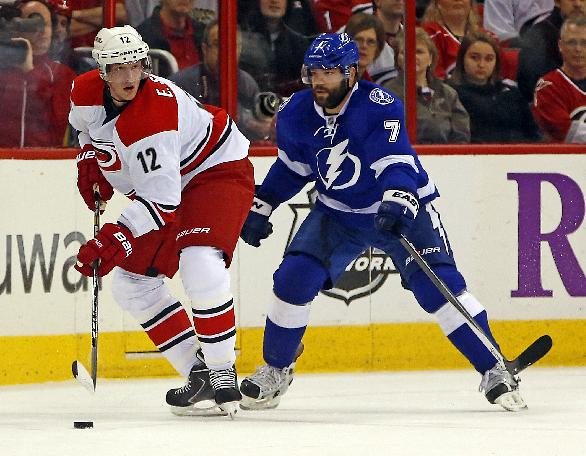 Carolina Hurricanes' Eric Staal (12) looks to pass the puck as Tampa Bay Lightning's Radko Gudas (7) defends during the first period of an NHL hockey game, Friday, Nov. 1, 2013, in Raleigh, N.C