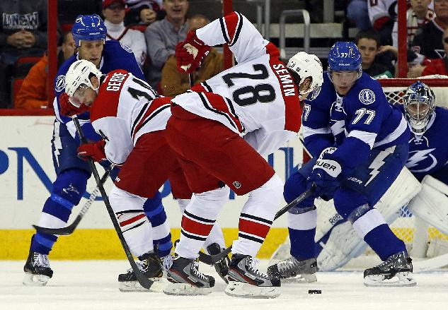 Carolina Hurricanes' Alexander Semin (28) of Russia, battles with Tampa Bay Lightning's Victor Hedman (77) as Hurricanes' Nathan Gerbe (14) and Lightning's Sami Salo (6) of Finland, battle for position during the first period of an NHL hockey game, Friday, Nov. 1, 2013, in Raleigh, N.C