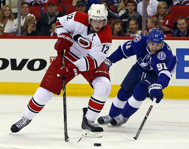 Carolina Hurricanes' Eric Staal (12) works the puck against Tampa Bay Lightning's Steven Stamkos (91) during the second period of an NHL hockey game in Raleigh, N.C., Friday, Nov. 1, 2013. Lightning won 3-0