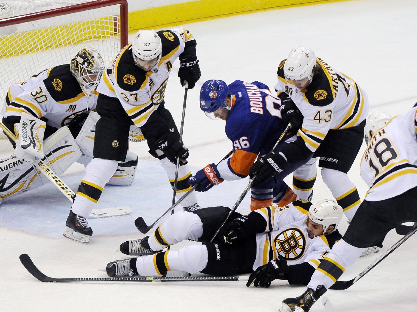 Boston Bruins' Patrice Bergeron (37),  Matt Bartkowski (43), Reilly Smith (18) surround New York Islanders' Pierre-Marc Bouchard (96) as Bouchard tries to retrieve the puck under Boston Bruins' Adam McQuaid (54) in the first period of an NHL hockey game at the Nassau Coliseum on Saturday, Nov. 2, 2013, in Uniondale, N.Y