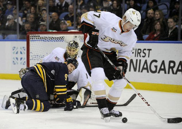 Anaheim Ducks defenseman Hampus Lindholm, (47), of Sweden, carries the puck past fallen Buffalo Sabres center Steve Ott (9) and goaltender Jonas Hiller (1) of the Czech Republic, during the first period of an NHL hockey game in Buffalo, N.Y., Saturday, Nov. 2, 2013