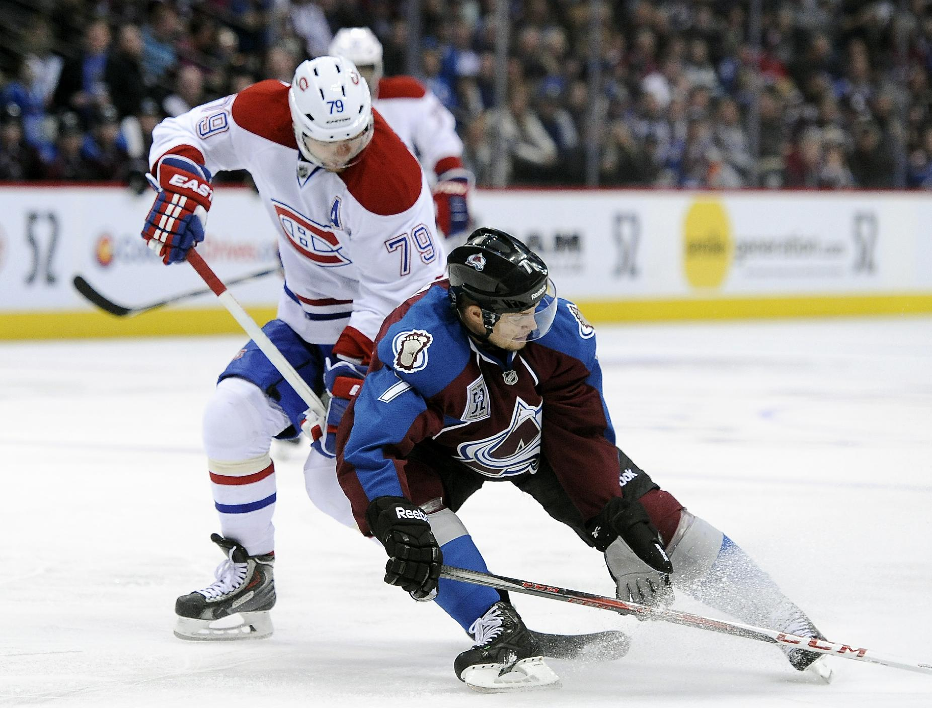 Colorado Avalanche center John Mitchell, right, tries to steal the puck from Montreal Canadiens defenseman Andrei Markov, left, of Russia, in the second period of an NHL hockey game on Saturday, Nov. 2, 2013, in Denver