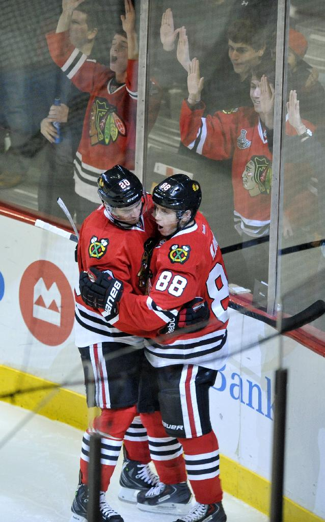 Chicago Blackhawks' Patrick Kane (88), celebrates with teammate Brandon Saad after scoring a goal during the second period of an NHL hockey game against the Calgary Flames in Chicago, Sunday, Nov. 3, 2013