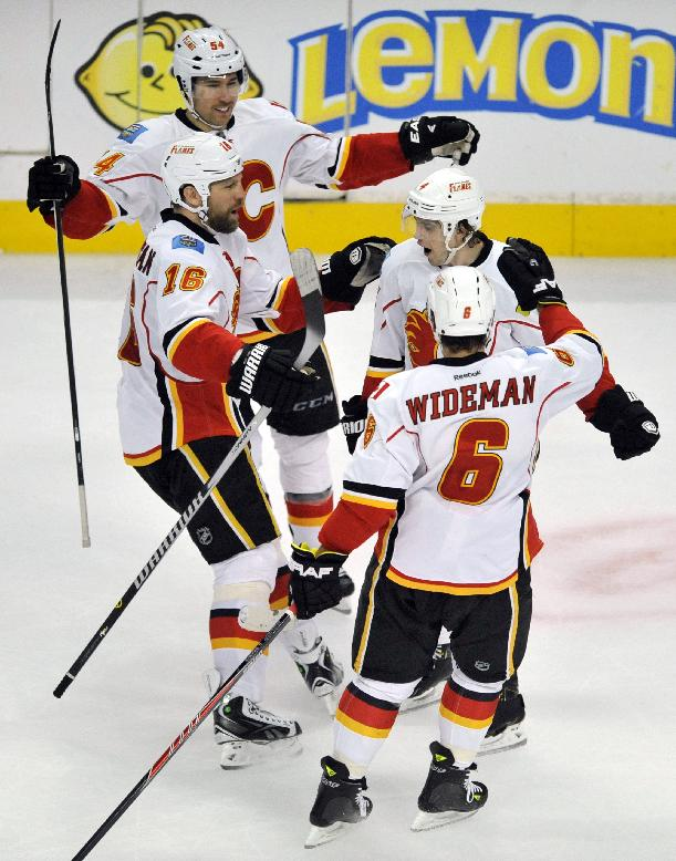 Calgary Flames' Kris Russell, top right, celebrates with teammates Brian McGrattan (16), Dennis Wideman (6), and David Jones after Russell scored the winning goal to defeat the Chicago Blackhawks 3-2 during overtime of an NHL hockey game in Chicago, Sunday, Nov. 3, 2013