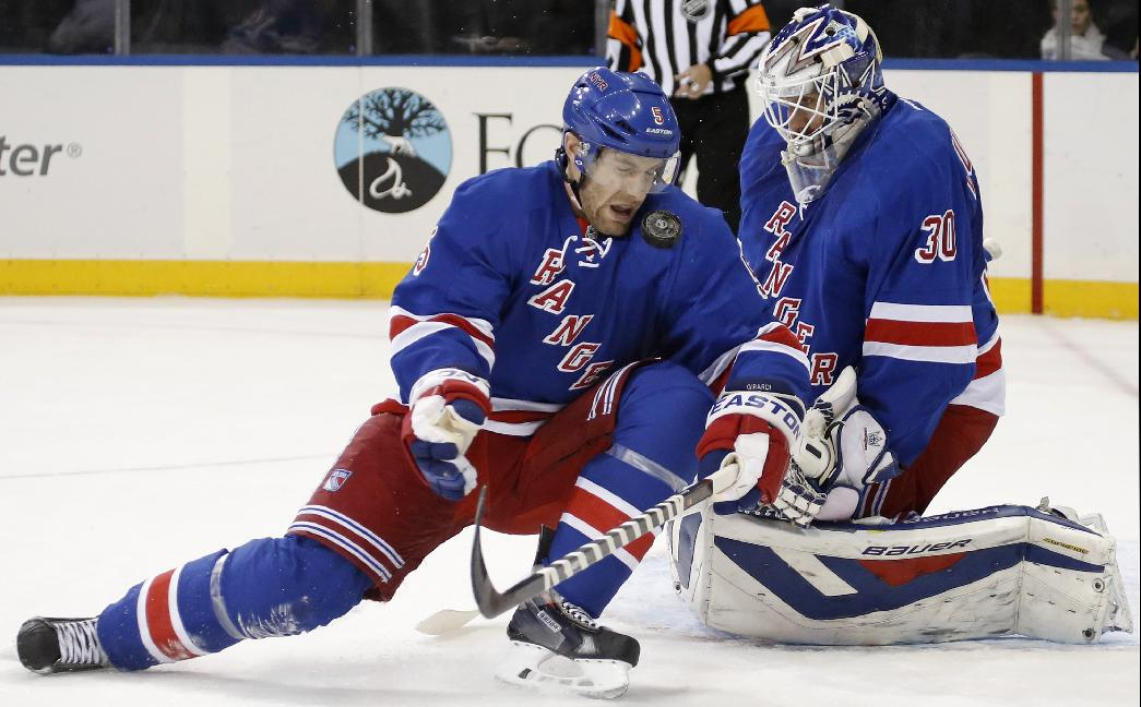 New York Rangers defenseman Dan Girardi (5) blocks a shot in front of New York Rangers goalie Henrik Lundqvist (30) of Sweden in the first period of an NHL hockey game at Madison Square Garden in New York, Monday, Nov. 4, 2013
