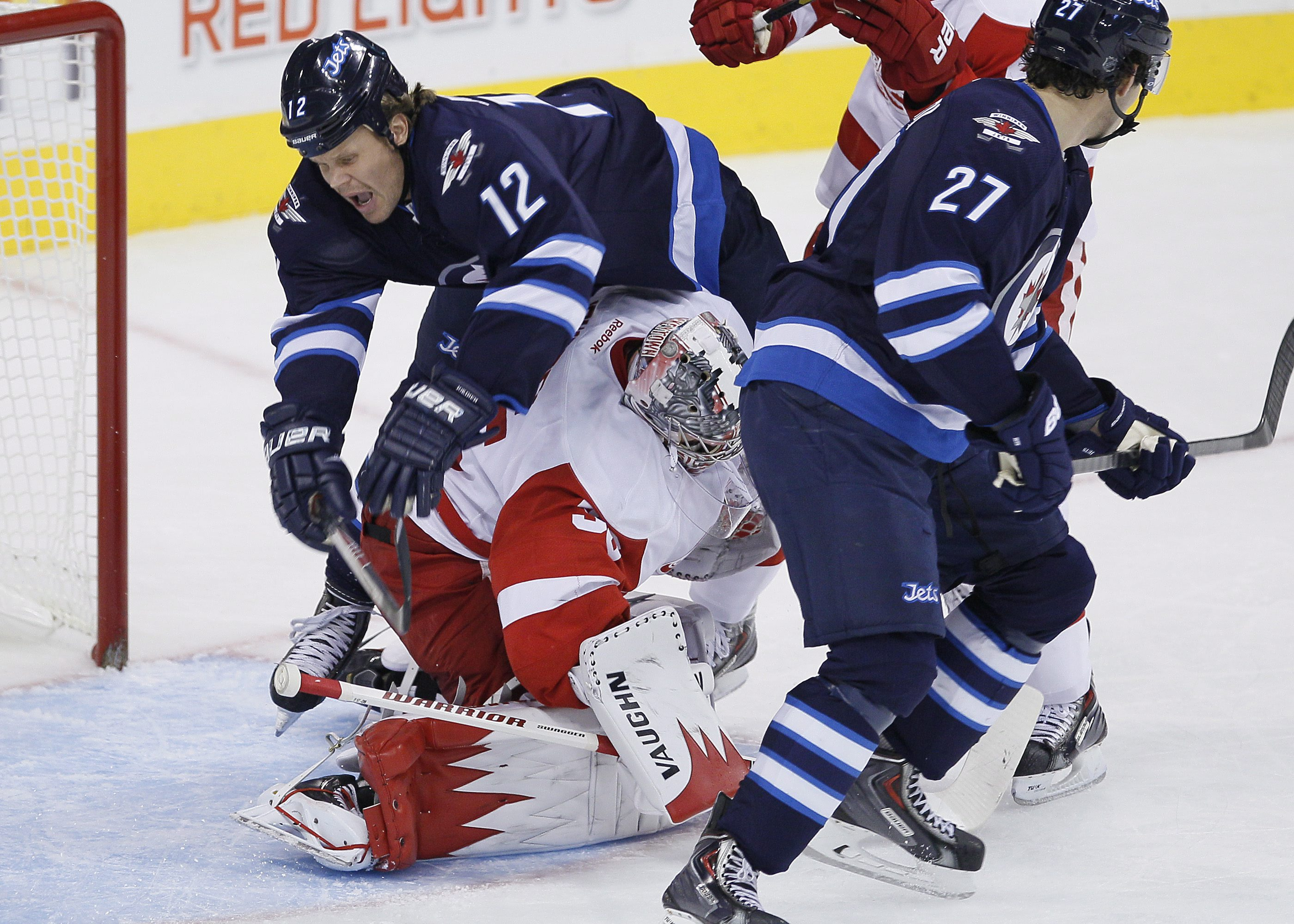 Winnipeg Jets' Olli Jokinen (12) goes over the top of Detroit Red Wings' goaltender Jimmy Howard (35) during first period NHL action in Winnipeg on Monday, Nov. 4, 2013