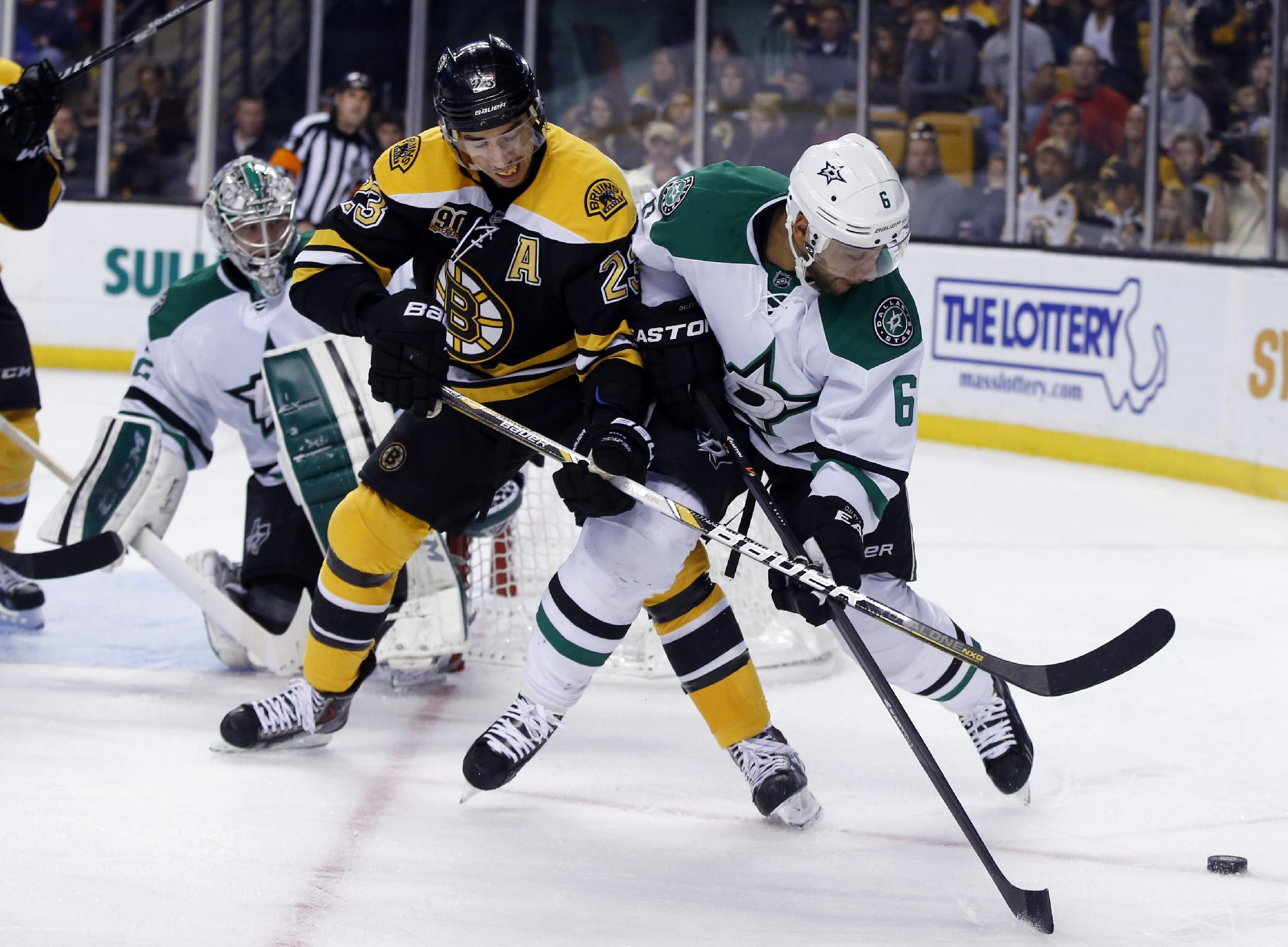Boston Bruins center Chris Kelly (23) tries to gain control of the puck as Dallas Stars defenseman Trevor Daley (6) defends while Stars goalie Kari Lehtonen watches at left during the second period of an NHL hockey game in Boston, Tuesday, Nov. 5, 2013
