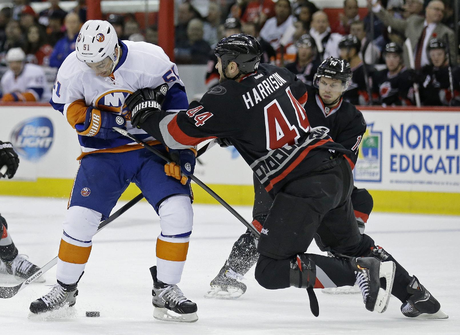 Carolina Hurricanes' Jay Harrison (44) defends against New York Islanders' Frans Nielsen (51), of Denmark, during the first period of an NHL hockey game in Raleigh, N.C., Thursday, Nov. 7, 2013
