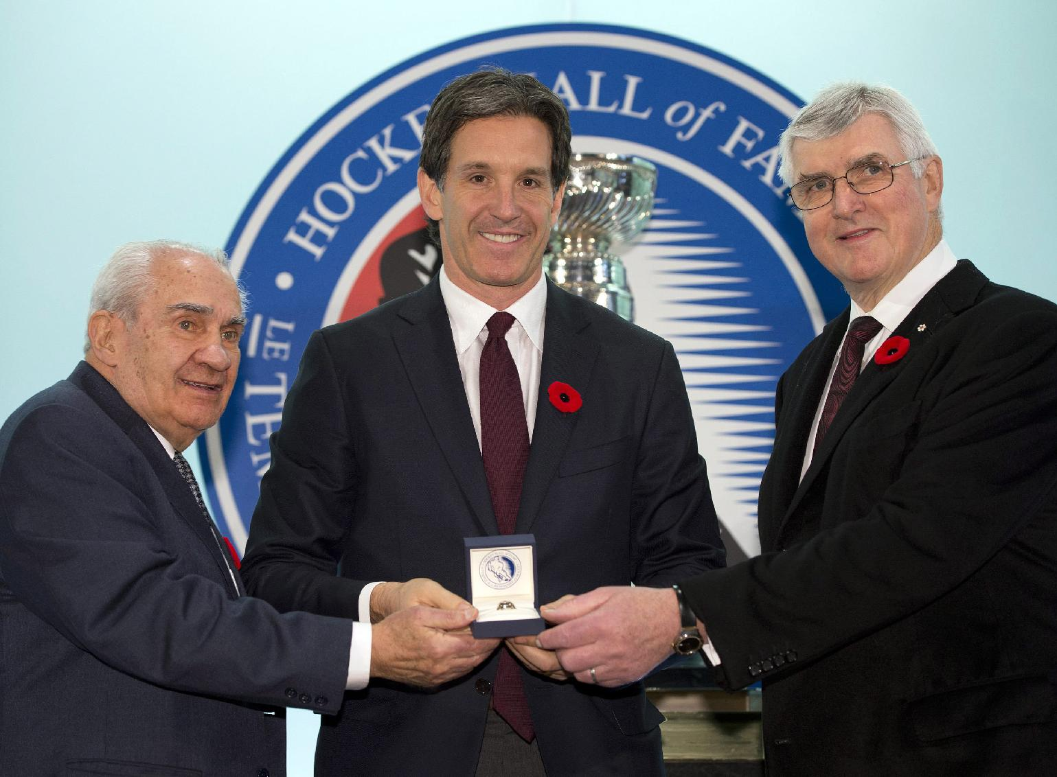 Hockey Hall of Fame inductee Brendan Shanahan is presented with his ring by Hall of Fame Chairman Pat Quinn , right, and Chair of the selection committee Jim Gregory  is presented with his ring by Hockey Hall of Fame Chairman Pat Quinn at the Hall in Toronto on Friday, Nov. 8, 2013
