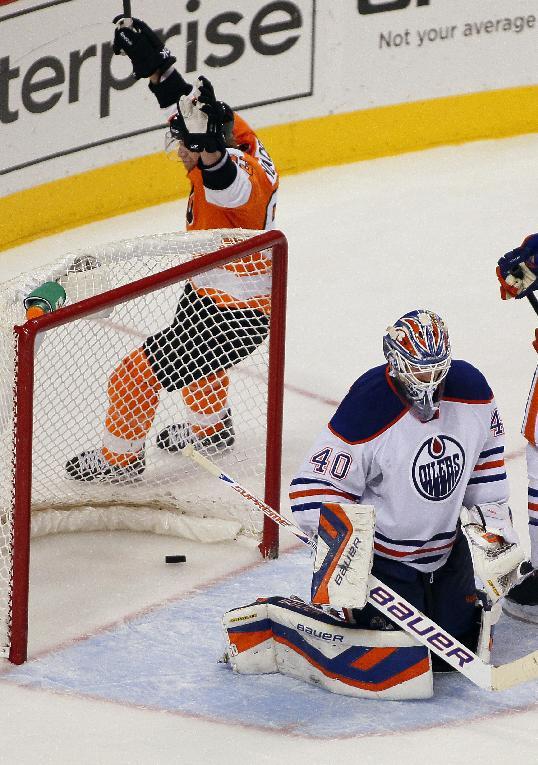 Philadelphia Flyers' Jakub Voracek raises his arms circling the net where a goal by Claude Giroux lays behind Edmonton Oilers goalie Devan Dubnyk during the third period of an NHL hockey game, Saturday, Nov. 9, 2013, in Philadelphia. The Flyers won 4-2