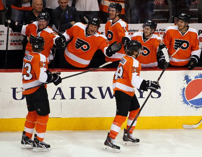 Philadelphia Flyers' captain Claude Giroux, right, who scored his first goal of the season, is followed by Jakub Voracek, who got the assist,  as they skate past their teammates on the bench during the third period of an NHL hockey game with the Edmonton Oilers, Saturday, Nov. 9, 2013, in Philadelphia. The Flyers won 4-2