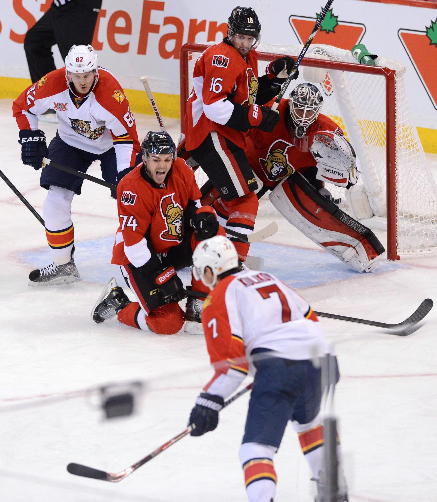 Ottawa Senators' Mark Borowiecki (74) drops to a knee as he attempts to block a shot from Florida Panthers' Dmitry Kulikov during the third period of an NHL hockey game in Ottawa, Ontario, on Saturday, Nov. 9, 2013