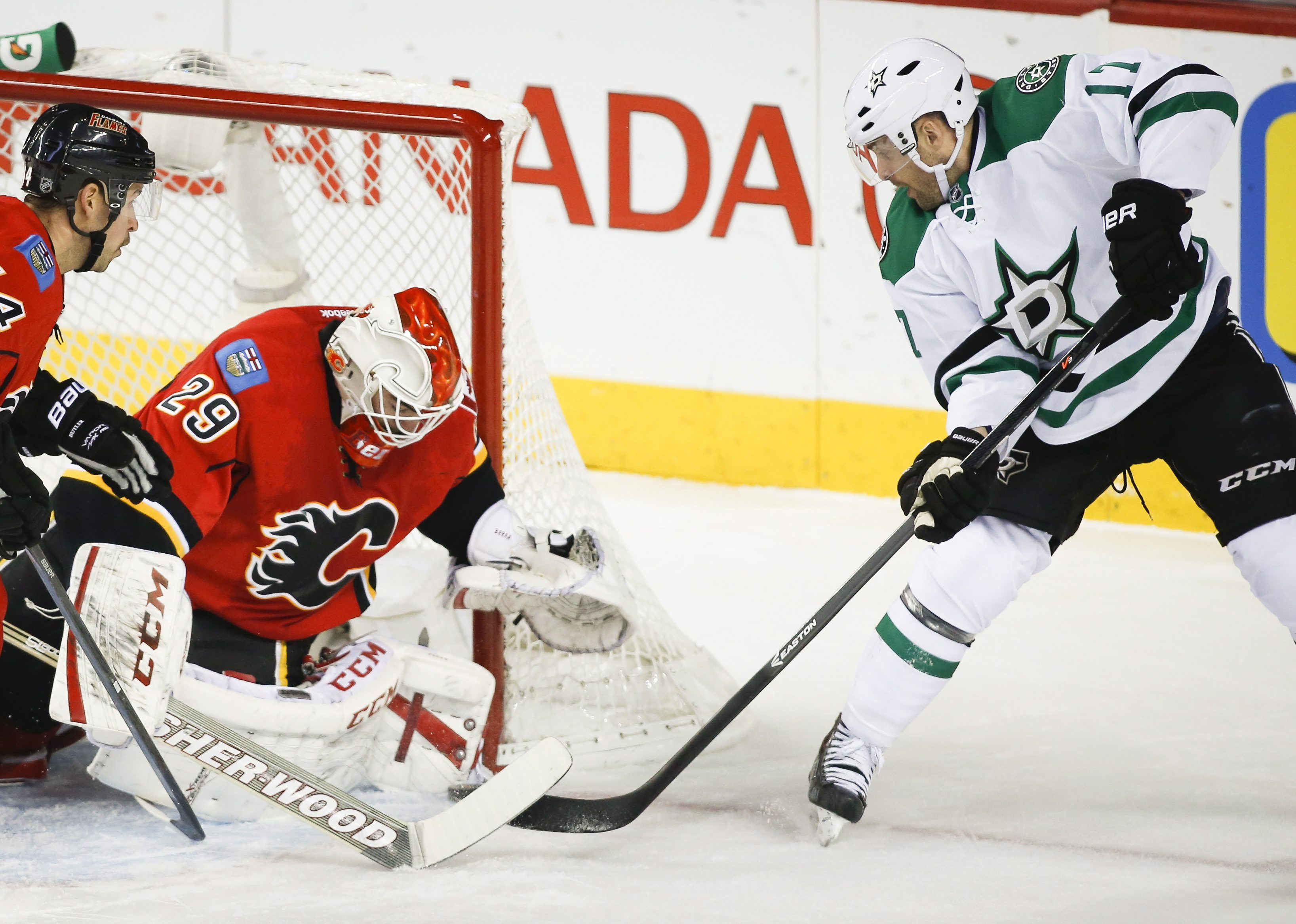 Dallas Stars' Rich Peverley, right, tries to get the puck past Calgary Flames goalie Reto Berra, from Switzerland, during first-period NHL hockey game action in Calgary, Alberta., Thursday, Nov. 14, 2013