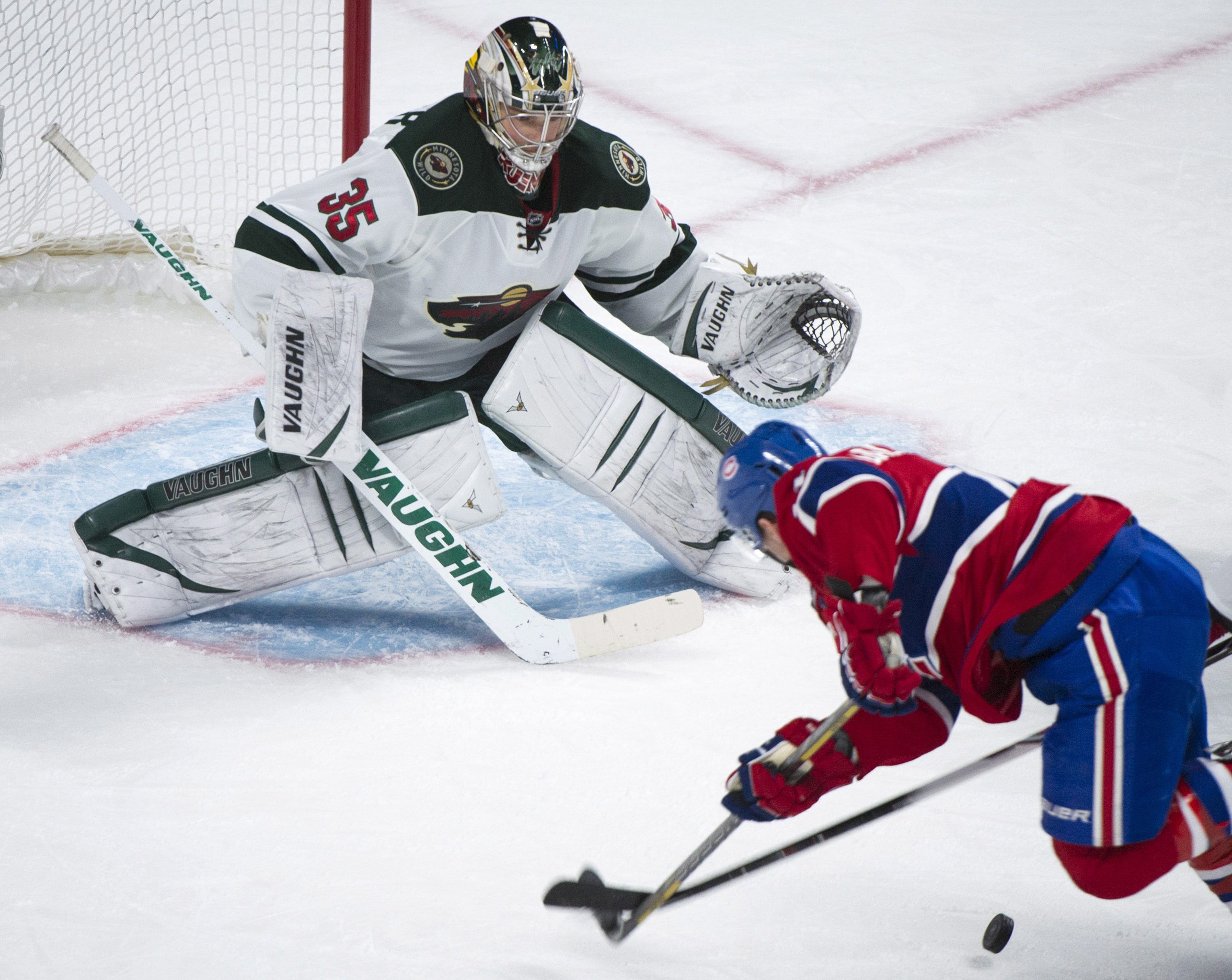 Montreal Canadiens' Brendan Gallagher trips as he moves in on Minnesota Wild's goaltender Darcy Kuemper, left, during the third period of an NHL hockey game Tuesday, Nov. 19, 2013 in Montreal