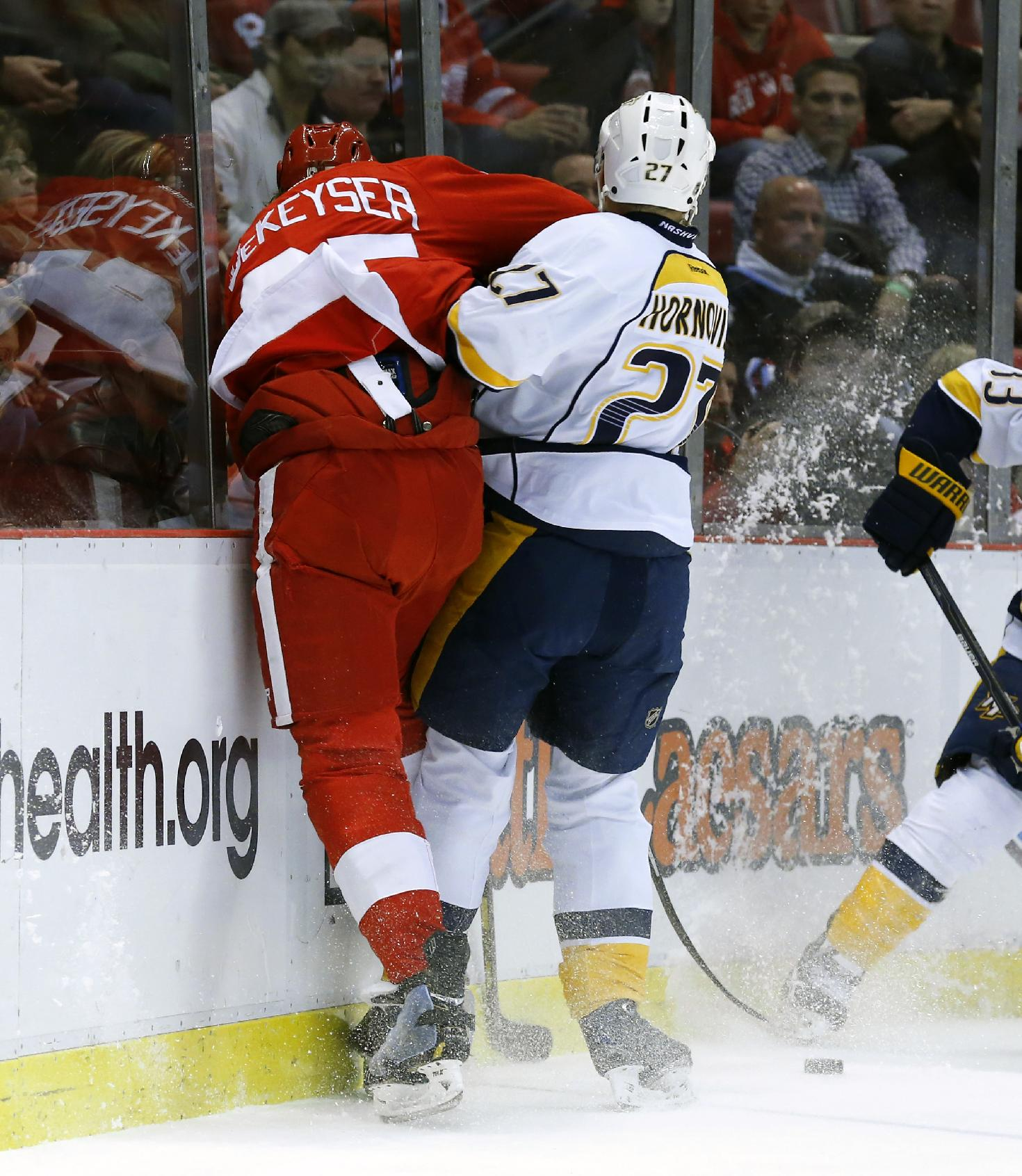 In this photo taken Nov. 19, 2013, Detroit Red Wings defenseman Danny DeKeyser, left, is checked into the boards by Nashville Predators right wing Patric Hornqvist (27), of Sweden, in the first period of an NHL hockey game in Detroit. DeKeyser is expected to  be out for at least three to four weeks with a separated left shoulder due to the hit