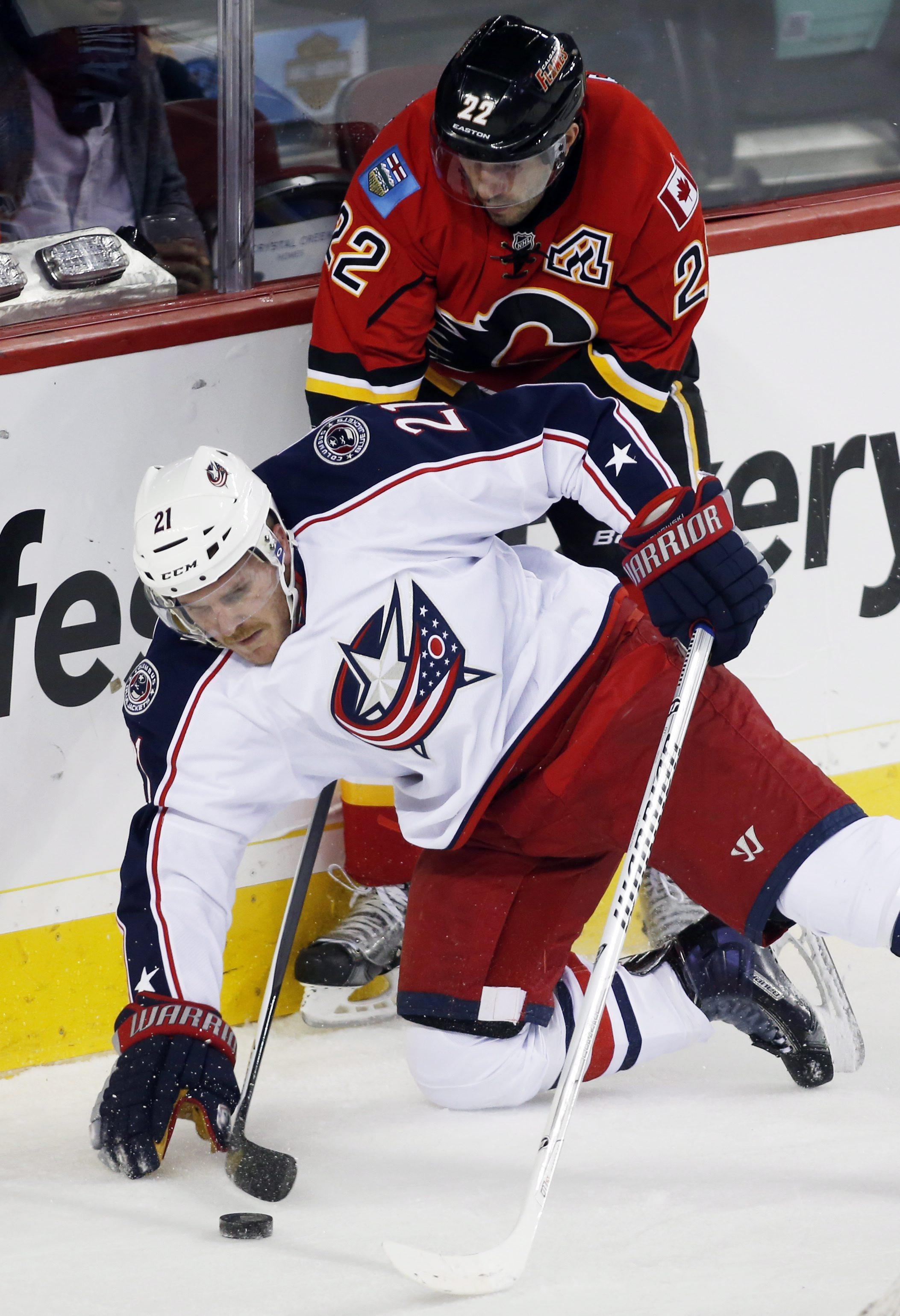 Columbus Blue Jackets' James Wisniewski, left, falls on the stick of Calgary Flames' Lee Stempniak during first period NHL hockey action in Calgary, Alberta, Wednesday, Nov. 20, 2013