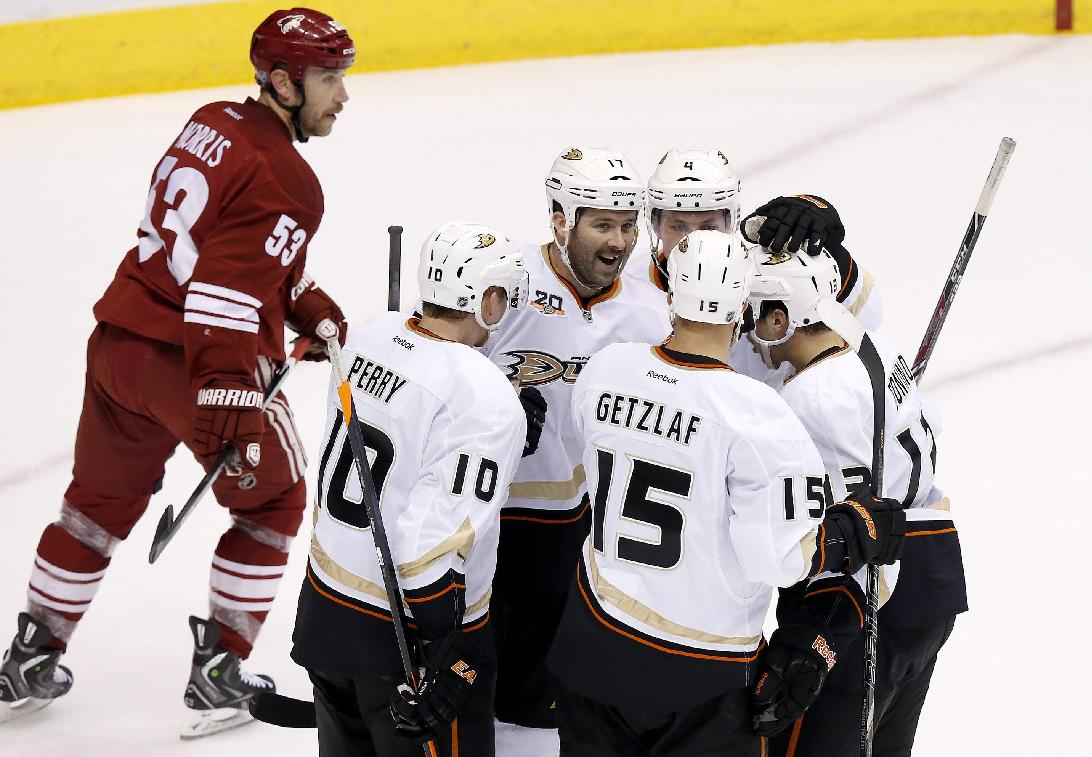 Anaheim Ducks' Dustin Penner (17) celebrates his goal against the Phoenix Coyotes with teammates Corey Perry (10), Ryan Getzlaf (15), Cam Fowler (4) and Nick Bonino, right, as Phoenix Coyotes' Derek Morris (53) skates past during the first period of an NHL hockey game Saturday, Nov. 23, 2013, in Glendale, Ariz