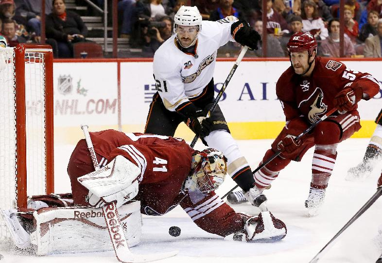 Phoenix Coyotes' Mike Smith (41) makes a save on a shot as Anaheim Ducks' Kyle Palmieri (21) and Coyotes' Derek Morris, right, both stand by during the second period of an NHL hockey game Saturday, Nov. 23, 2013, in Glendale, Ariz