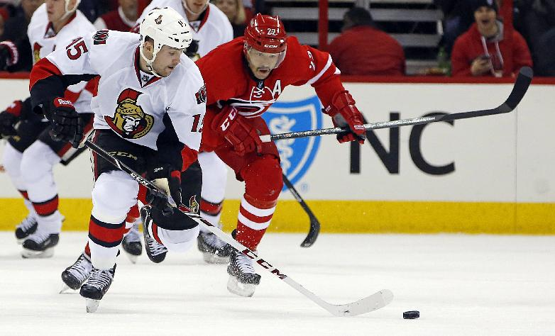 Ottawa Senators' Zack Smith, left, moves the puck down the ice with Carolina Hurricanes' Manny Malhotra giving chase during the first period of an NHL hockey game in Raleigh , N.C., Sunday, Nov. 24, 2013