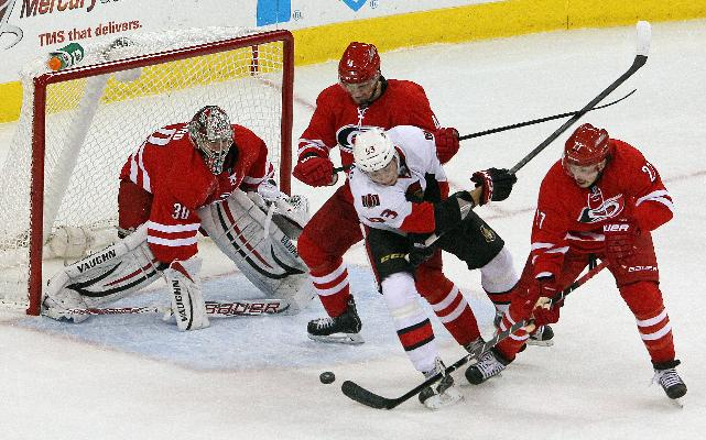 Ottawa Senators' Mika Zibanejad (93) battles between Carolina Hurricanes defenders Justin Faulk (27), and Andrej Sekera, second from left, in front of goalie Cam Ward (30) during the third period of an NHL hockey game in Raleigh, N.C., Sunday, Nov. 24, 2013. Hurricanes won 4-1