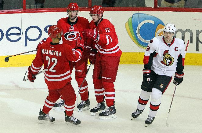 Carolina Hurricanes' Eric Staal (12) celebrates his empty-net goal with teammates Radek Dvorak, second from left, and Manny Malhotra (22) as Ottawa Senators' Jason Spezza, right, skates by during the third period of an NHL hockey game in Raleigh, N.C., Sunday, Nov. 24, 2013. Hurricanes won 4-1