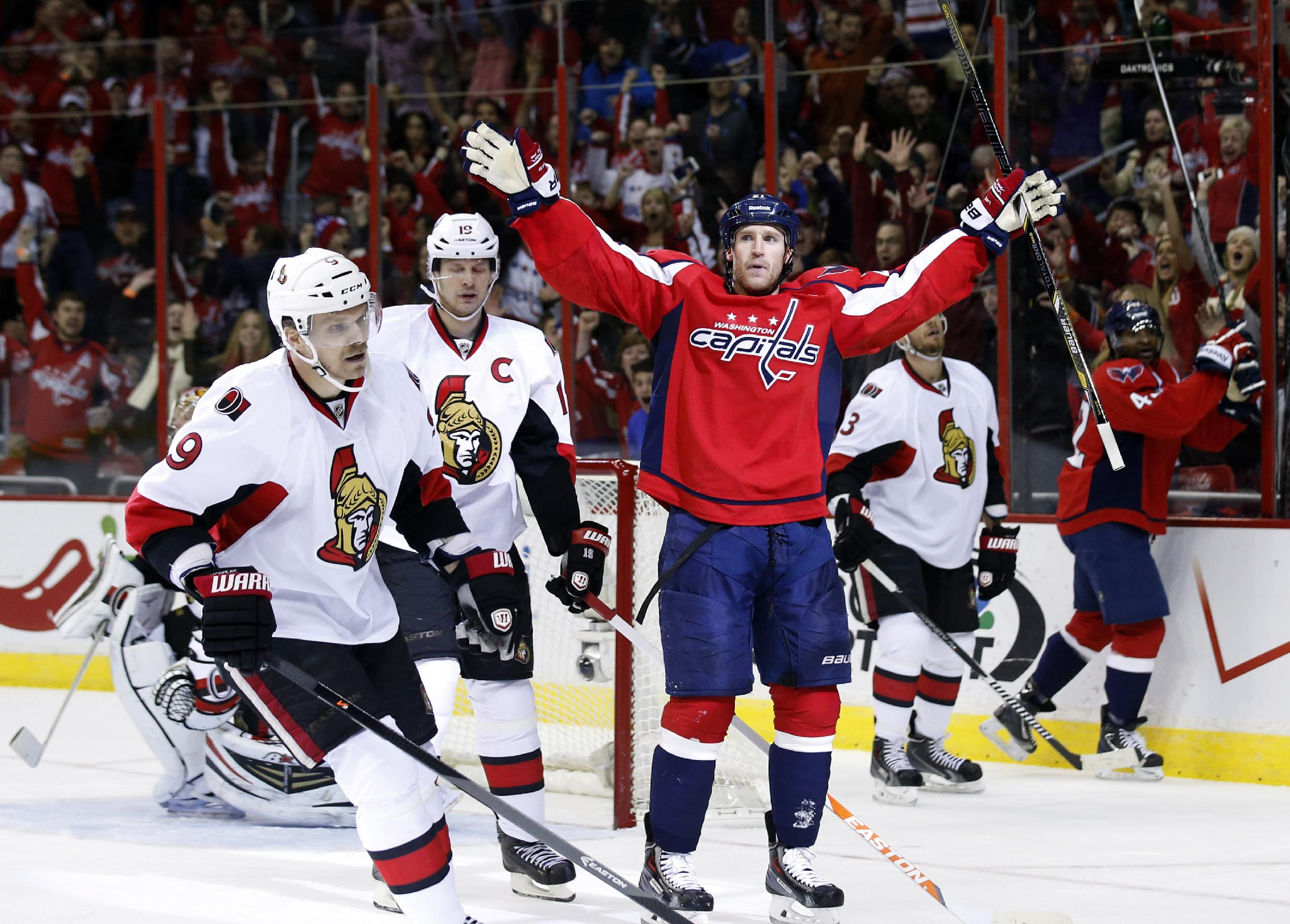 Washington Capitals center Brooks Laich (21) celebrates his goal as Ottawa Senators left wing Milan Michalek (9), from the Czech Republic, and center Jason Spezza (19) skate nearby in the first period of an NHL hockey game, Wednesday, Nov. 27, 2013, in Washington