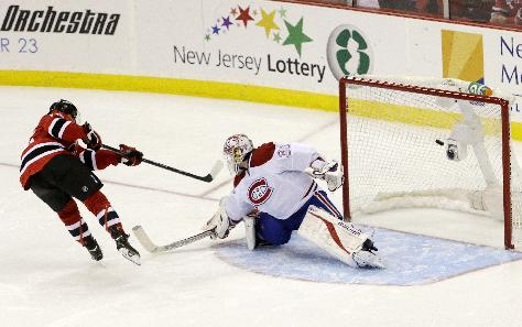 New Jersey Devils left wing Reid Boucher, left, scores a shootout goal during his NHL debut on a shot against Montreal Canadiens goalie Peter Budaj, of Slovakia, during an NHL hockey game, Wednesday, Dec. 4, 2013, in Newark, N.J. The Canadiens won 4-3