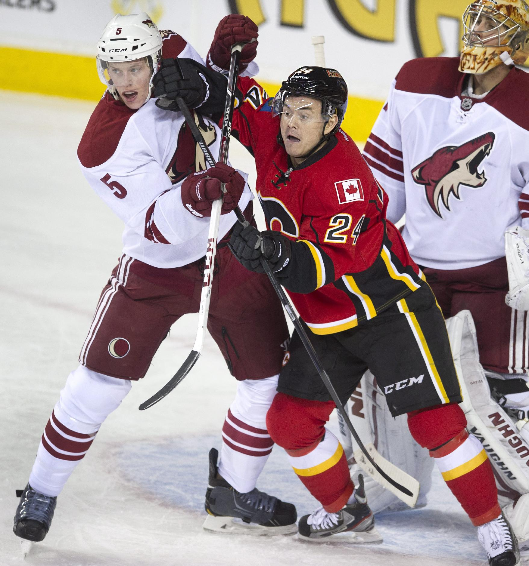 Phoenix Coyotes' Connor Murphy, left, battles with Calgary Flames' Jiri Hudler, from Czech Republic, in front of Phoenix goalie Thomas Greiss, from Germany, during the first period of an NHL hockey game, Wednesday, Dec. 4, 2013 in Calgary, Alberta