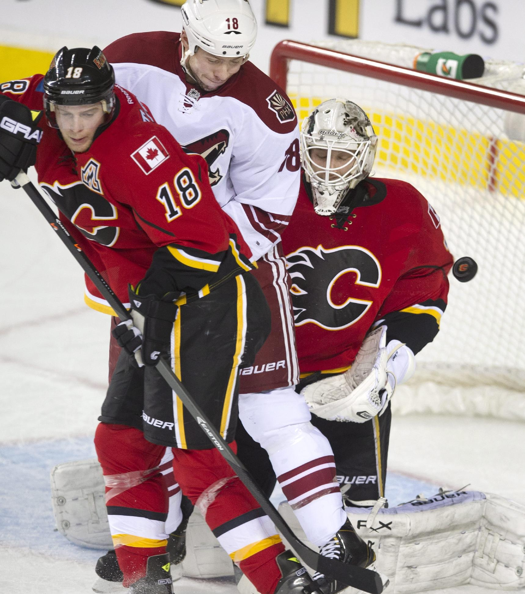 Calgary Flames' goalie, Reto Berra, right, from Finland, makes a save as Calgary's Matt Stajan, left, battles with Phoenix Coyotes' David Moss during second period NHL action Wednesday, Dec. 4, 2013 in Calgary, Alberta