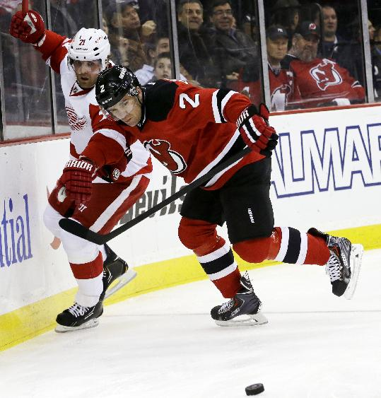 New Jersey Devils defenseman Marek Zidlicky (2), of Czech Republic, and Detroit Red Wings right wing Daniel Cleary compete for the puck during the first period of an NHL hockey game Friday, Dec. 6, 2013, in Newark, N.J