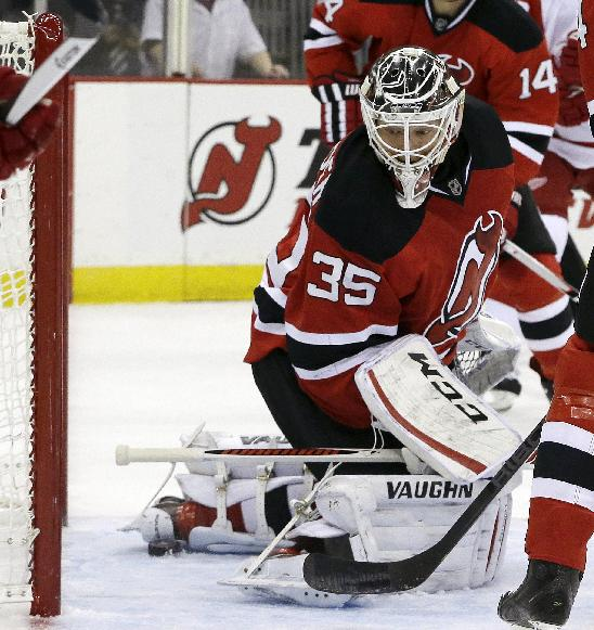 The puck stops shy of the goal line at the heel of New Jersey Devils goalie Cory Schneider during the first period of an NHL hockey game against the Detroit Red Wings, Friday, Dec. 6, 2013, in Newark, N.J