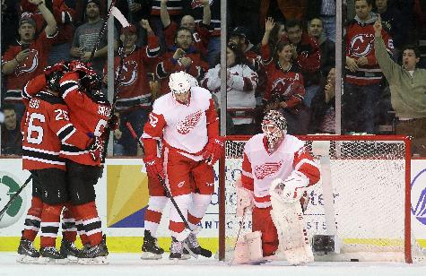 New Jersey Devils players celebrate a goal by defenseman Andy Greene as Detroit Red Wings goalie Jonas Gustavsson, right, of Sweden, and defenseman Jonathan Ericsson, of Sweden, are nearby during the first period of an NHL hockey game Friday, Dec. 6, 2013, in Newark, N.J