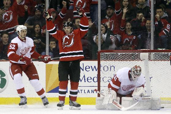 New Jersey Devils defenseman Andy Greene, left, celebrates after scoring a goal against Detroit Red Wings goalie Jonas Gustavsson, right, of Sweden, as defenseman Jonathan Ericsson (52), of Sweden, stands by during the first period of an NHL hockey game Friday, Dec. 6, 2013, in Newark, N.J