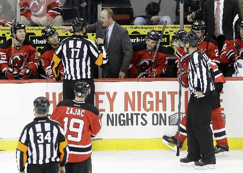 New Jersey Devils head coach Peter DeBoer, center right, challenges a call with referee Frederick L'Ecuyer (17) during the third period of an NHL hockey game against the Detroit Red Wings, Friday, Dec. 6, 2013, in Newark, N.J. The Red Wings won 3-1