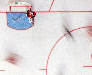 In this photograph taken with a long shutter which blurs objects in motion, New Jersey Devils goalie Cory Schneider (35) stands in his crease while players and officials skate before the start of an NHL hockey game against the Detroit Red Wings, Friday, Dec. 6, 2013, in Newark, N.J. The Red Wings won 3-1