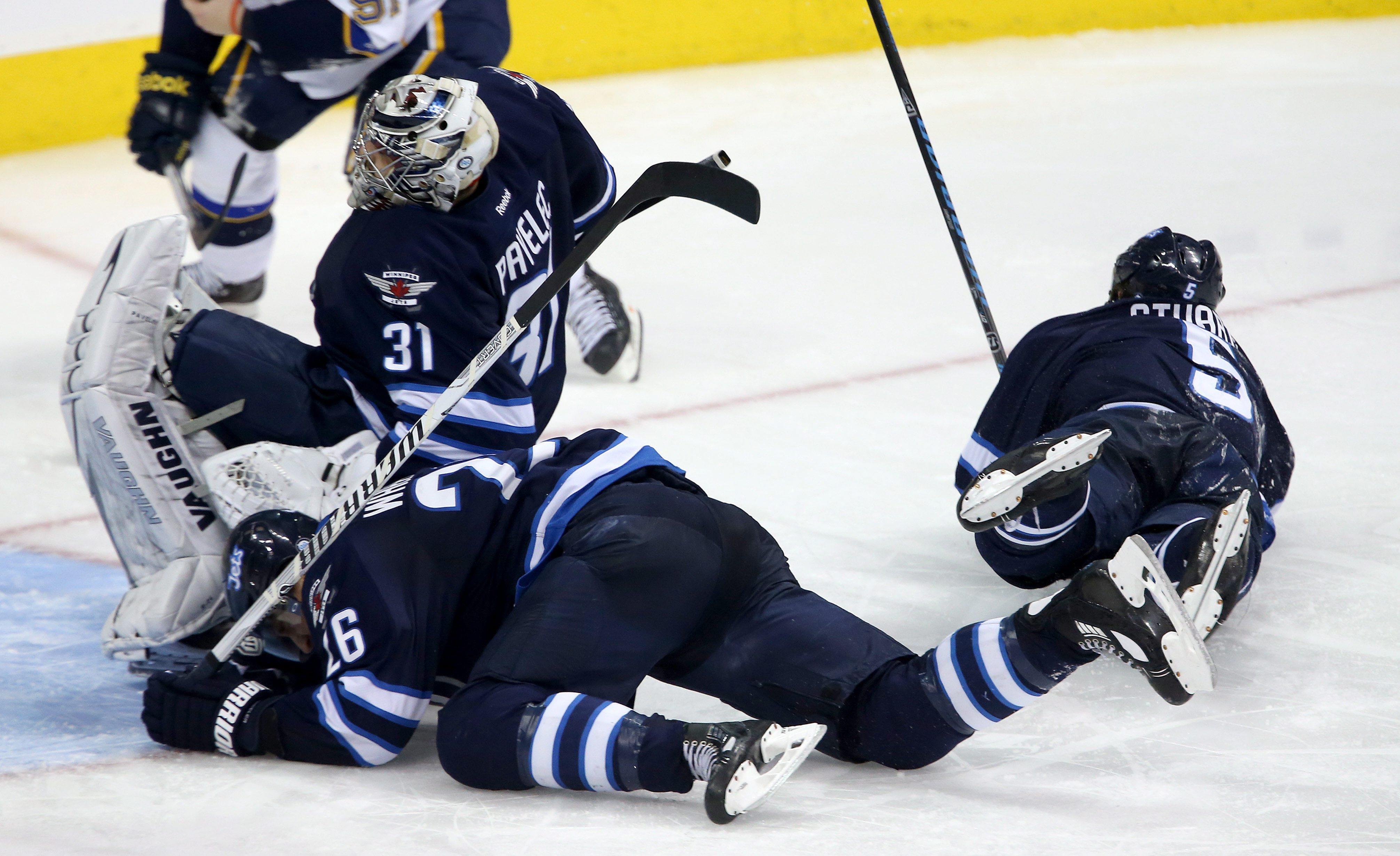 Winnipeg Jets' goaltender Ondrej Pavelec (31) falls onto Blake Wheeler (26) as Mark Stuart (5) lays on the ice nearby during third period NHL hockey action against the St. Louis Blues' in Winnipeg, Tuesday,  Dec. 10, 2013