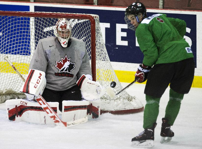 Team Canada goalie Jake Paterson, left, makes a save against Canada forward Connor McDavid, right, in practice during the start of world juniors selection camp in Toronto on Friday, Dec. 13, 2013