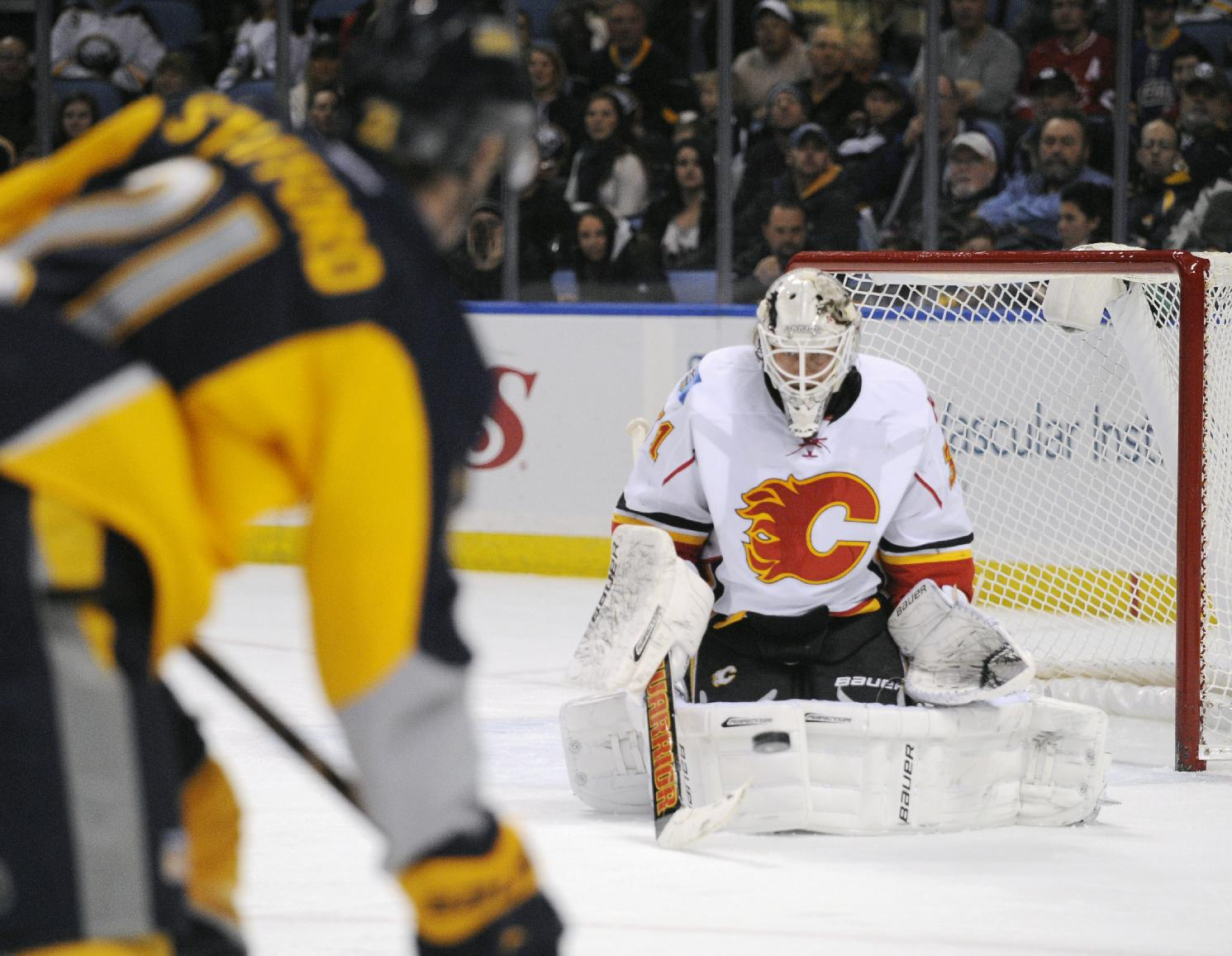 Buffalo Sabres right wing Drew Stafford (21) shoots the puck at Calgary Flames goaltender Karri Ramo (31), of Finland, during the first period of an NHL hockey game in Buffalo, N.Y., Saturday Dec. 14, 2013. Calgary won 2-1