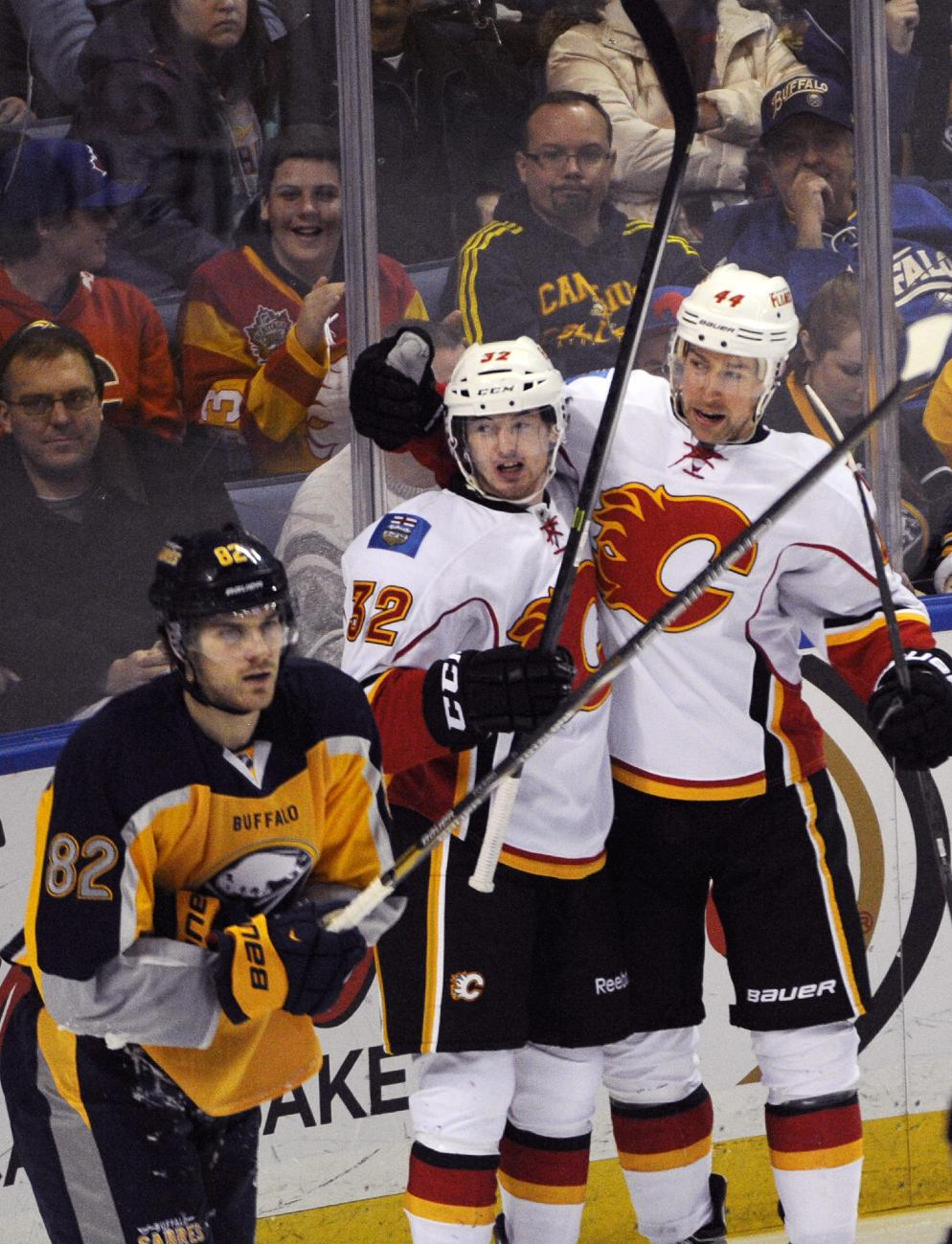 Buffalo Sabres' Marcus Foligno (82) reacts after a goal by Calgary Flames' Paul Byron (32) as Byron celebrates with Chris Butler (44) during the third period of an NHL hockey game in Buffalo, N.Y., Saturday Dec. 14, 2013. Calgary won in overtime 2-1